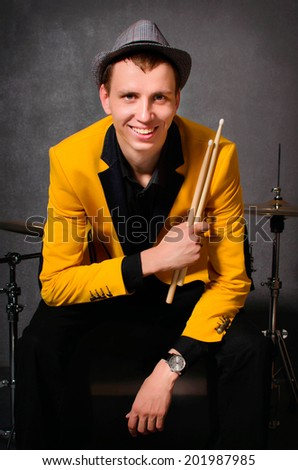 Handsome drummer in hat and yellow jacket with drumsticks. Portrait of expressive young drummer man with his drum set studio shot - stock photo