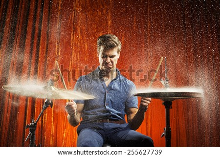 Handsome drummer man playing on cymbal with drops water  - stock photo