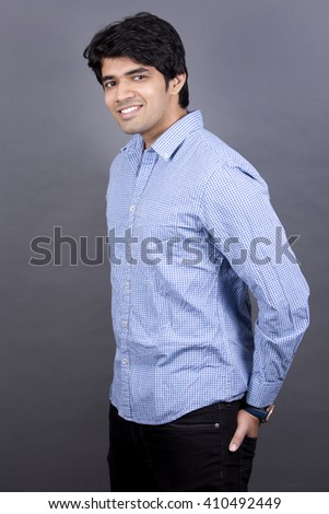 handsome east indian man wearing blue shirt on light grey background