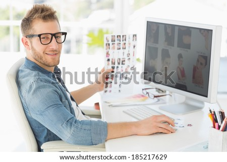 Handsome editor working at his computer smiling at camera in creative office - stock photo