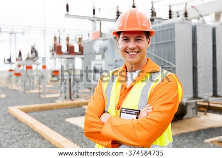 handsome electrical engineer arms crossed in substation - stock photo