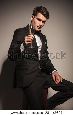 Handsome elegant business man offering you a glass of champagne while sitting on a chair. - stock photo