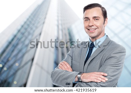 Handsome elegant businessman in front of office building - stock photo