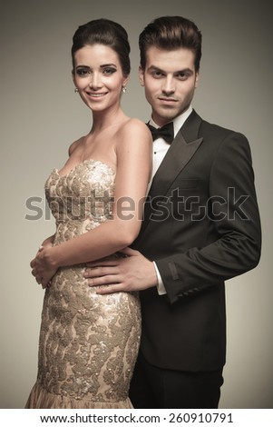 Handsome elegant man holding his lover close to him, both looking at the camera. - stock photo