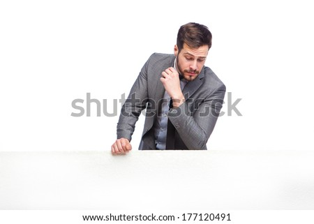 handsome elegant man looking down over the panel on white background - stock photo