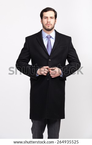 handsome elegant man with beard in black overcoat, isolated - stock photo