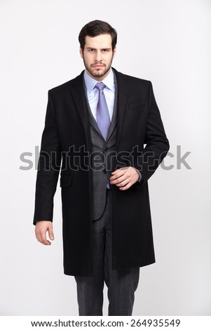 handsome elegant man with beard in black overcoat, isolated - stock photo