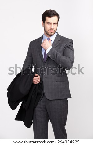 handsome elegant man with beard with overcoat in hand dressed in gray suit, isolated