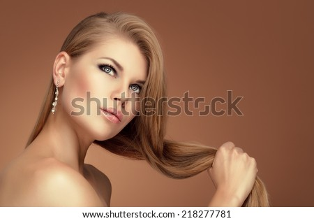 Handsome elegant model wearing jewelery touching her long healthy hair. Beautiful young Caucasian woman with professional make up and hairstyle posing in studio.  - stock photo