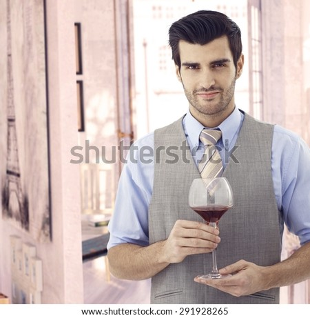 Handsome elegant young caucasian man with glass of wine at Paris retro home. Smiling standing, bristly, looking at camera. Suit and tie. Copyspace. - stock photo