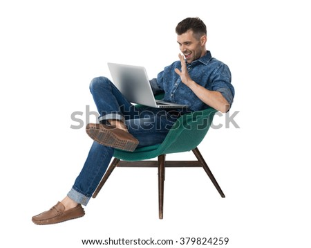 Handsome emotional Man sitting on armchair and using laptop Portrait Isolated on White Background - stock photo