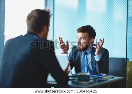 Handsome employee explaining his point of view to colleague at meeting - stock photo
