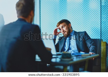 Handsome employee thinking of idea during talk with his colleague - stock photo