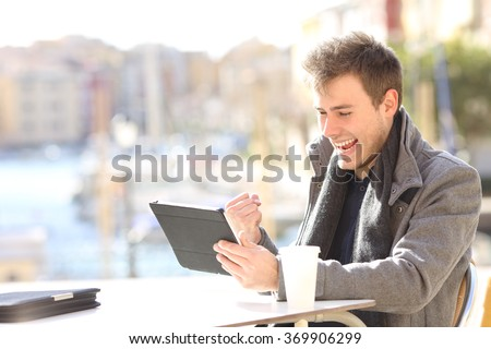 Handsome euphoric winner winning and watching a tablet in a coffee shop terrace of a port of urbanization with the sea in the background - stock photo