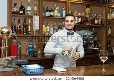 Handsome european bartender working at counter of night club