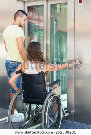 Handsome european man helping handicapped girlfriend at outdoor elevator
