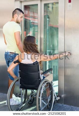 Handsome european man helping handicapped girlfriend at outdoor elevator - stock photo