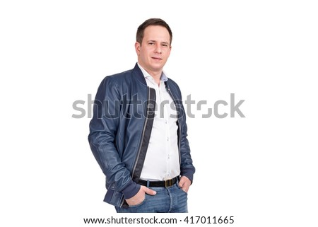 Handsome european man in white shirt, blue jeans and blue leather jacket. Holding hands in pockets while standing against white background - stock photo
