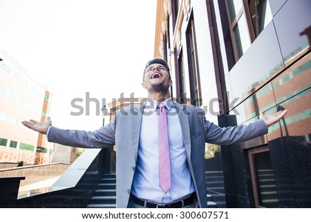 Handsome excited businessman celebrating his success outdoors - stock photo