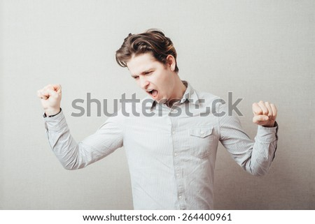 handsome excited man happy  hold arm hands fist raised up gesture, young guy wear shirt - stock photo