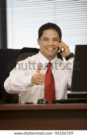 Handsome executive male giving thumbs-up in the office. - stock photo