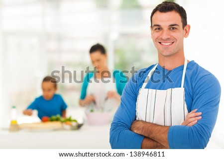 handsome family man standing in front of family in kitchen - stock photo