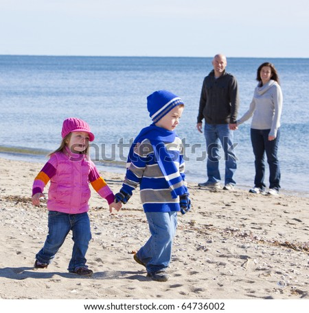 Handsome family walking at the beach with focus on little girl - stock photo