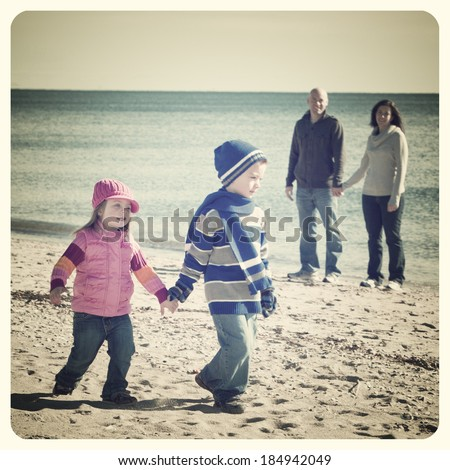 Handsome family walking at the beach with focus on little girl with Instagram effect filter  - stock photo