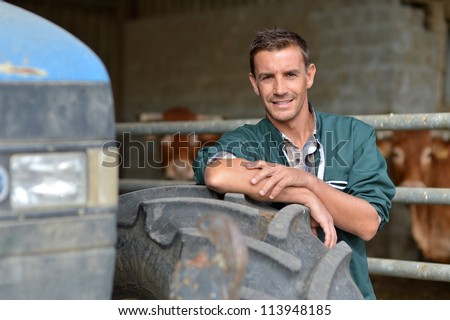 Handsome farmer leaning in barn on tractor wheel - stock photo