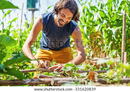 handsome  farmer mending a fence - stock photo