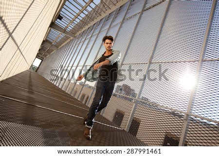 Handsome fashion male model dressed casual in a grungy location, wide and dynamic shots - stock photo
