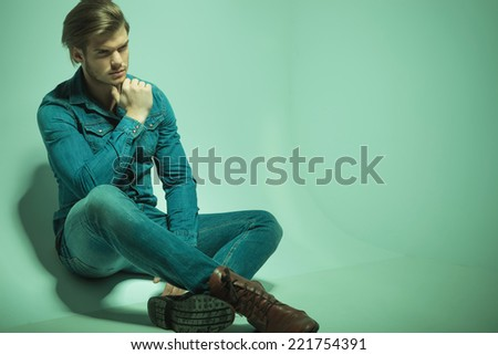 Handsome fashion man sitting on the floor, holding his hand to his chin while looking away from the camera. - stock photo