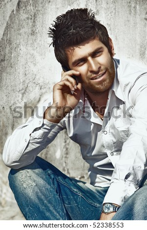 handsome fashion model in white cotton shirt and blue rugged jeans talking on the cell against grunge wall.