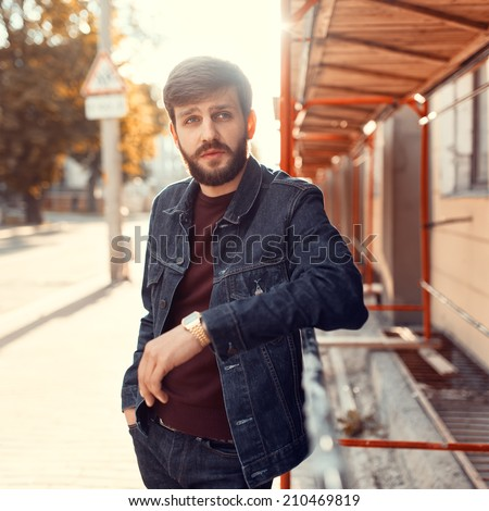 Handsome fashionable bearded man standing in the sunset on the street  - stock photo