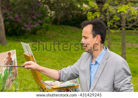 Handsome fashionable male artist during creation a masterpiece on a trestle and easel painting with oils and acrylics in a park - stock photo