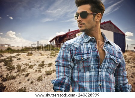 Handsome fashionable man in sunglasses and a blue checked shirt posing outdoors with a wooden cabin behind and copyspace looking into the center of the frame - stock photo