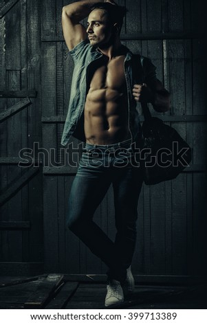 Handsome fashionable sexy sensual muscular young macho man with bare torso and stylish hair in jeans shirt holding sport bag indoor standing on wooden background, vertical picture - stock photo
