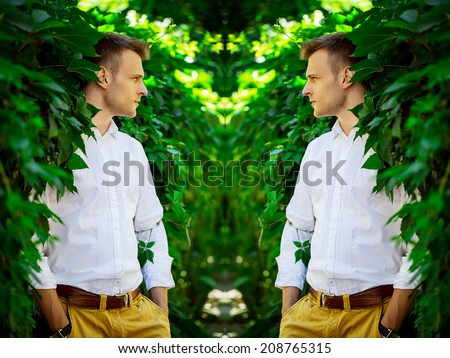 Handsome fashionable young man standing in the leaves of a wild grape. mirror reflection. - stock photo