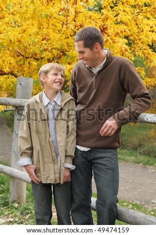 handsome father and son standing together outdoors in fall - stock photo