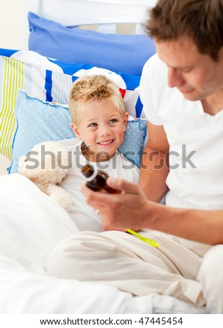Handsome father giving cough syrup to his sick son sitting on bed