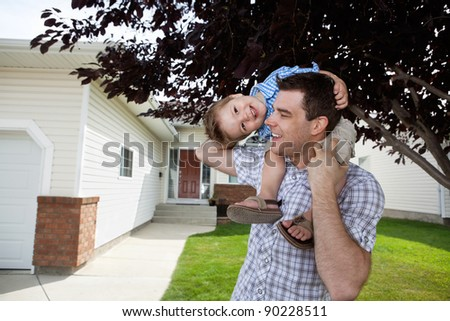 Handsome father with little son on his shoulders - stock photo
