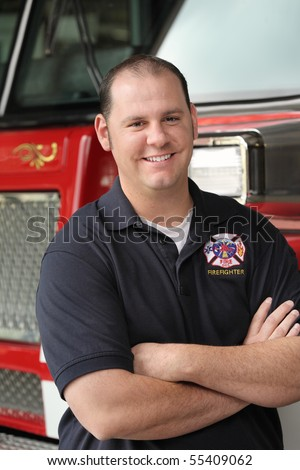 handsome fireman in his twenties with arms crossed standing in front of firetruck close-up - stock photo