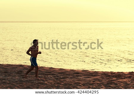 Handsome fit man running on the sunset beach, selective focus
