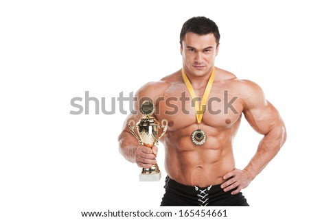 Handsome fit muscular man looking proud. Standing with cup and medal over white background