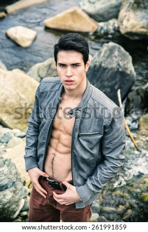 Handsome fit shirtless young man next to water pond or river, wearing grey leather jacket open on naked torso - stock photo