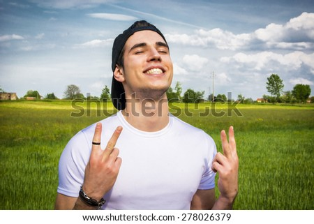 Handsome fit young man at countryside, in field or grassland, doing victory sign with fingers, smiling satisfied - stock photo