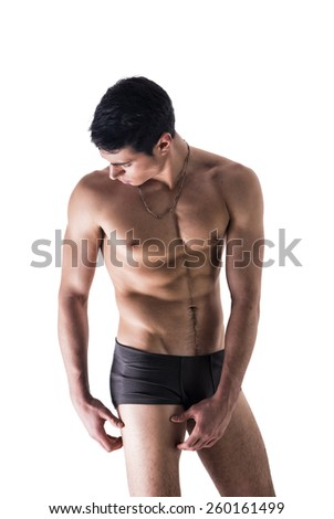 Handsome, fit young man wearing only underwear standing isolated on white background, looking down in a pose - stock photo