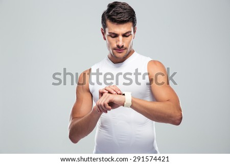 Handsome fitness man using smart watch over gray background - stock photo