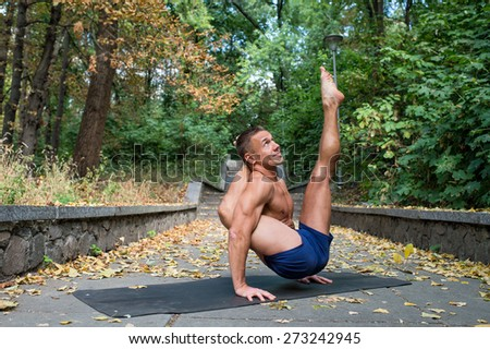 Handsome flexible Athletic man doing yoga asanas in the park in the fall