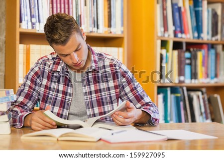 Handsome focused student studying his books in library - stock photo